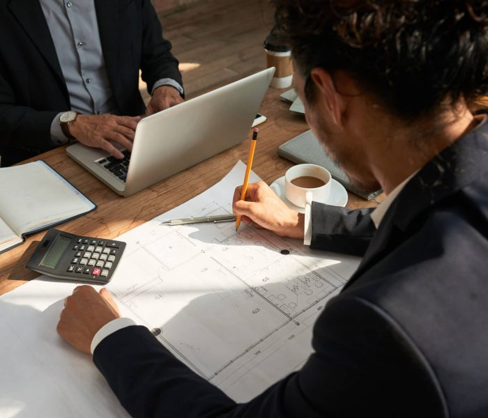 Engineer checking construction plan of office building on his table